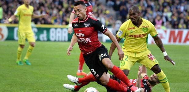 Marçal, do Guingamp (de vermelho e preto), disputa a bola com Nakoulma, do Nantes