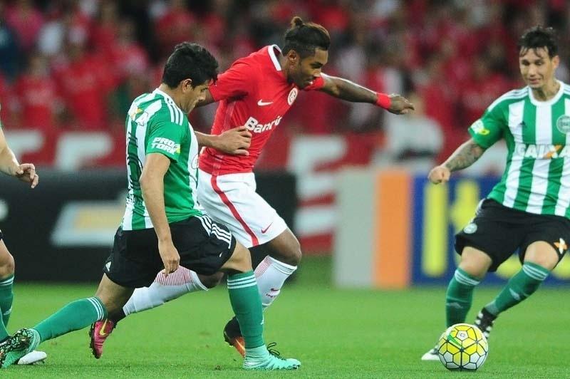 Vitinho tenta fugir da marcação de Benítez na partida Inter x Coritiba