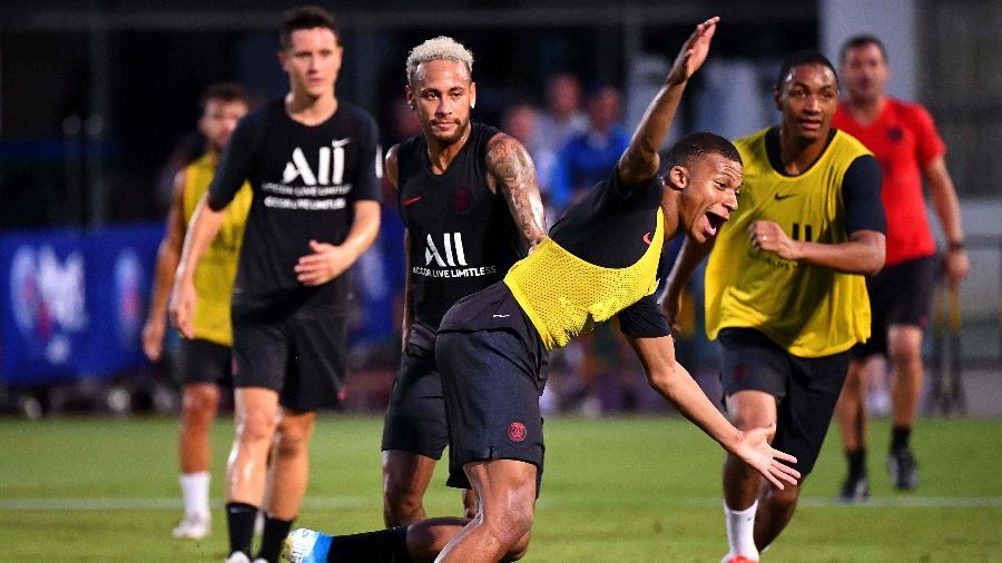 Neymar observa Mbappé durante treino do PSG na China - FRANCK FIFE / AFP
