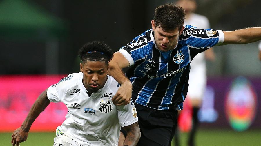 Marinho tenta se livrar da marcação de Kannemann durante Grêmio x Santos pela Libertadores 2020 - Diego Vara - Pool/Getty Images