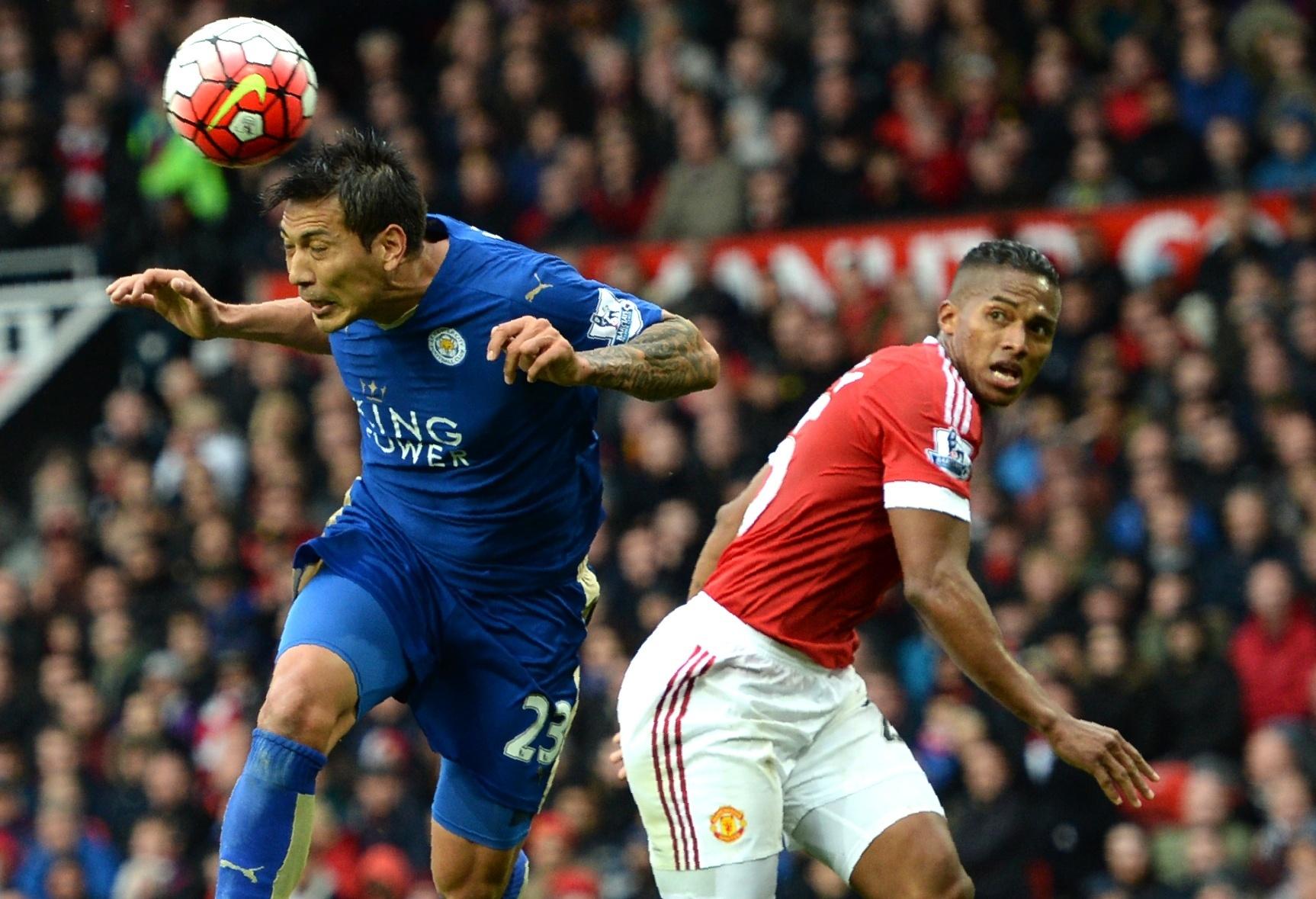 Ulloa, do Leicester, cabeceia a bola observado por Valencia, do Manchester United