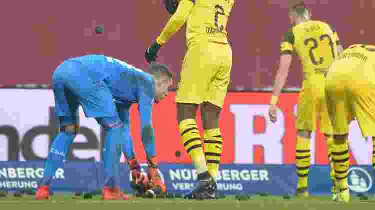 Jogadores recolhem bolinhas pretas arremessadas em jogo entre Borussia Dortmund e Nuremberg - TIMM SCHAMBERGER/AFP - TIMM SCHAMBERGER/AFP