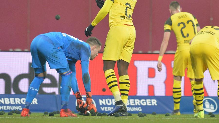 Jogadores recolhem bolinhas pretas arremessadas em jogo entre Borussia Dortmund e Nuremberg - TIMM SCHAMBERGER/AFP