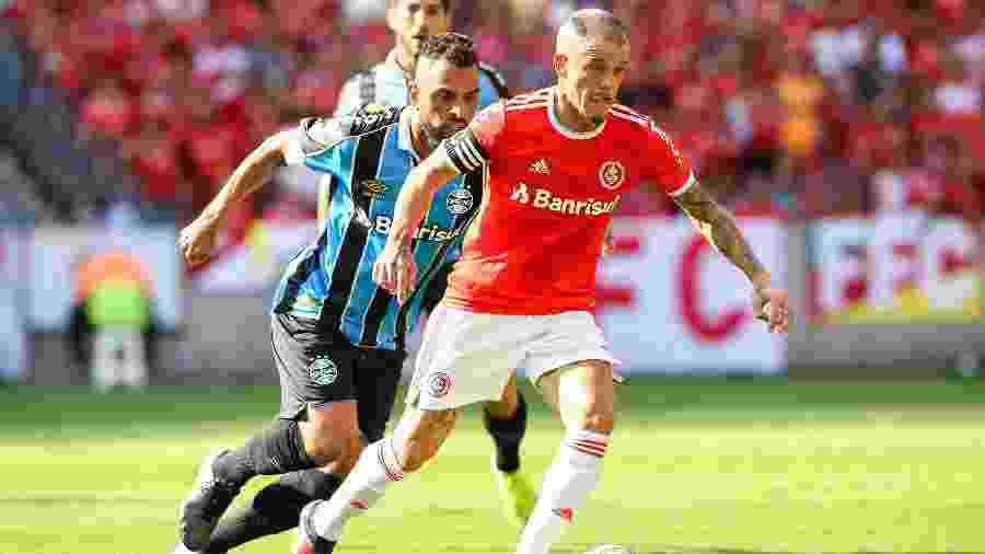 """D""""Alessandro, do Internacional, disputa lance com Maicon, do Grêmio, durante clássico - Pedro H. Tesch/AGIF"""
