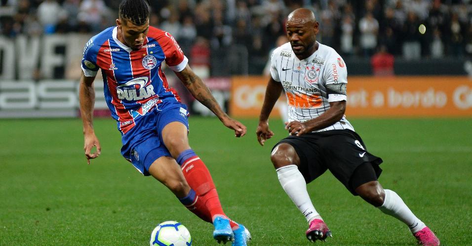 Juninho, jogador do Bahia, carrega a bola e é seguido por Vagner Love, do Corinthians