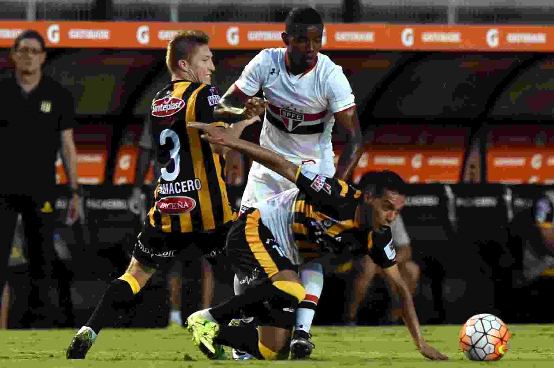 Thiago Mendes disputa a bola com dois jogadores do The Strongest - NELSON ALMEIDA/AFP