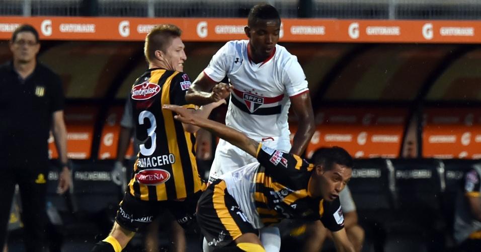 Thiago Mendes disputa a bola com dois jogadores do The Strongest