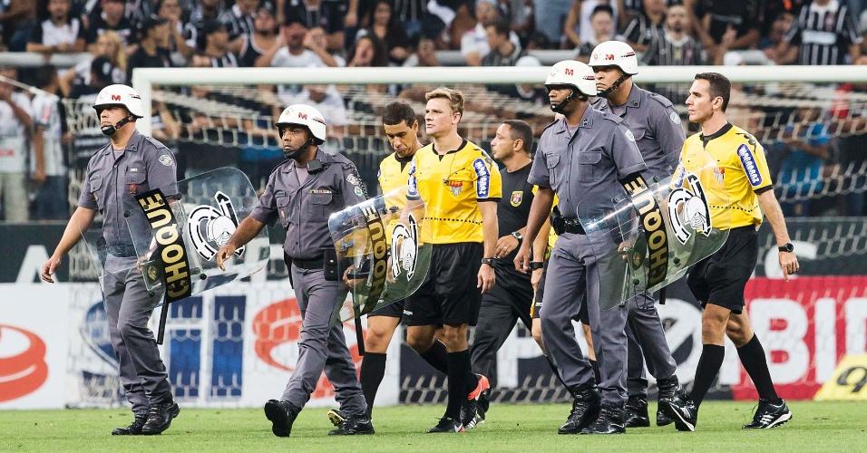 O árbitro Thiago Duarte Peixoto deixa o gramado da Arena Corinthians no intervalo cercado por policiais militares do Choque