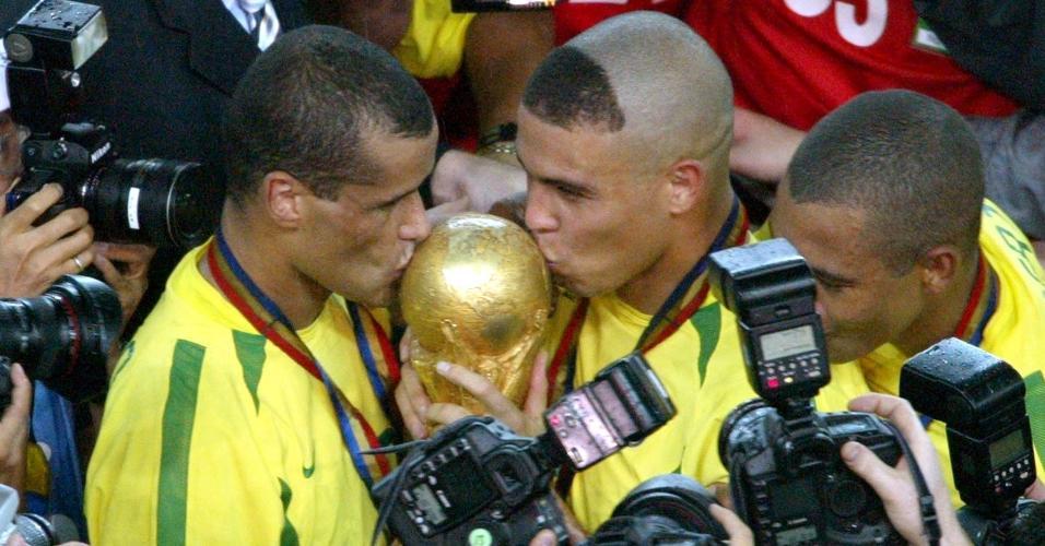 Rivaldo e Ronaldo beijam a taça da Copa do Mundo após a conquista do penta, em 2002