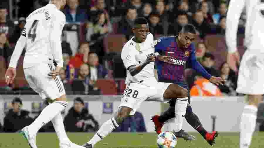 Vinicius Junior e Malcom disputam bola durante Barça x Real - Pau Barrena / AFP