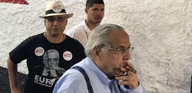 Eurico Miranda passeia pelo clube com seu charuto; camisa da chapa repete imagem