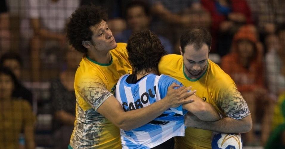 Thiagus tenta evitar jogada de argentino na final do handebol masculino