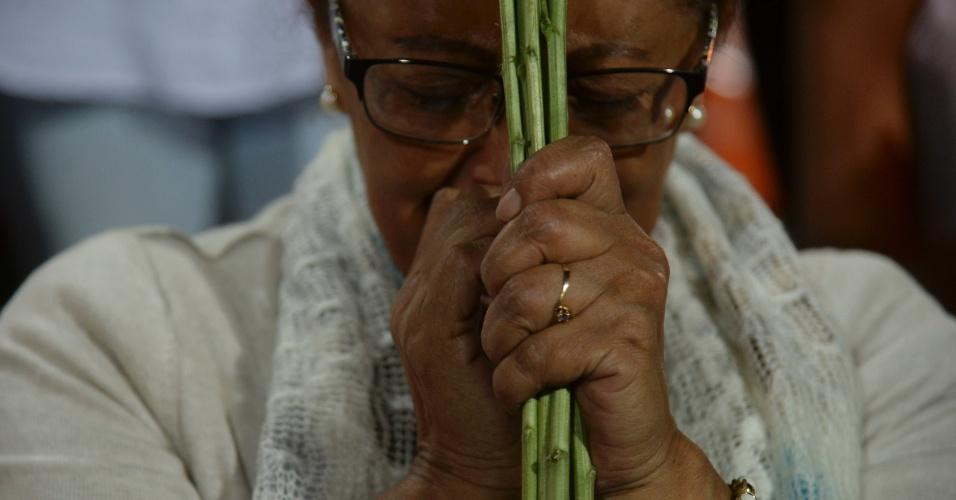 Mulher reza no estádio de Medellín pelos mortos no acidente aéreo na Colômbia