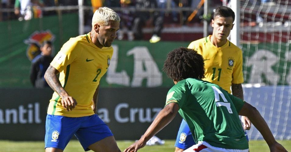 Daniel Alves tenta passar pela marcação de Juan Aponte no jogo entre Brasil e Bolívia