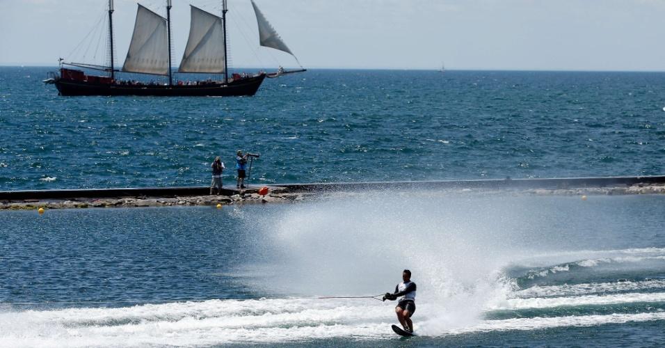 Adam Pickos compete pelo esqui aquático enquanto um navio passa ao fundo
