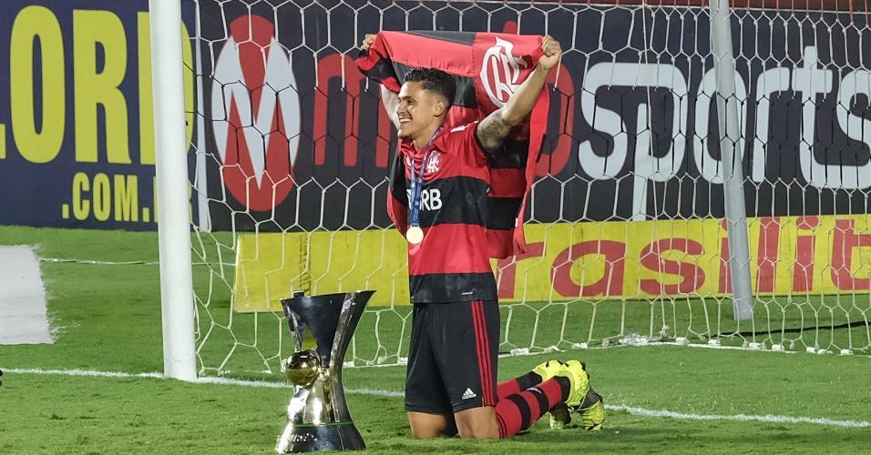 Pedro ajoelhado ao lado da taça do Brasileirão