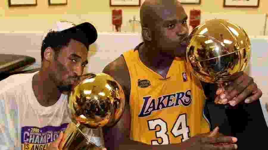 """Kobe Bryant (esq.) beija troféu de campeão da NBA, ao lado de Shaquille O""""Neal - Mike Blake/Reuters"""