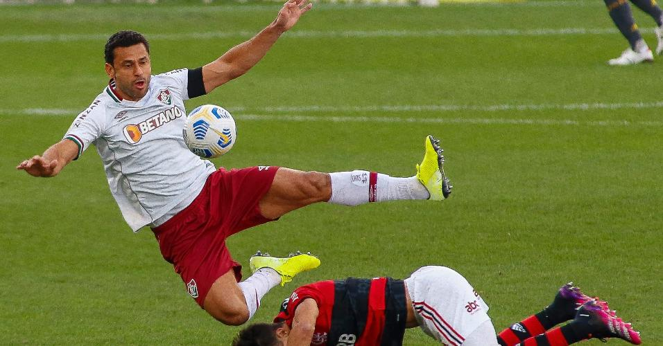 Fred cai após disputar uma bola com Rodrigo Caio, durante a partida entre Flamengo e Fluminense