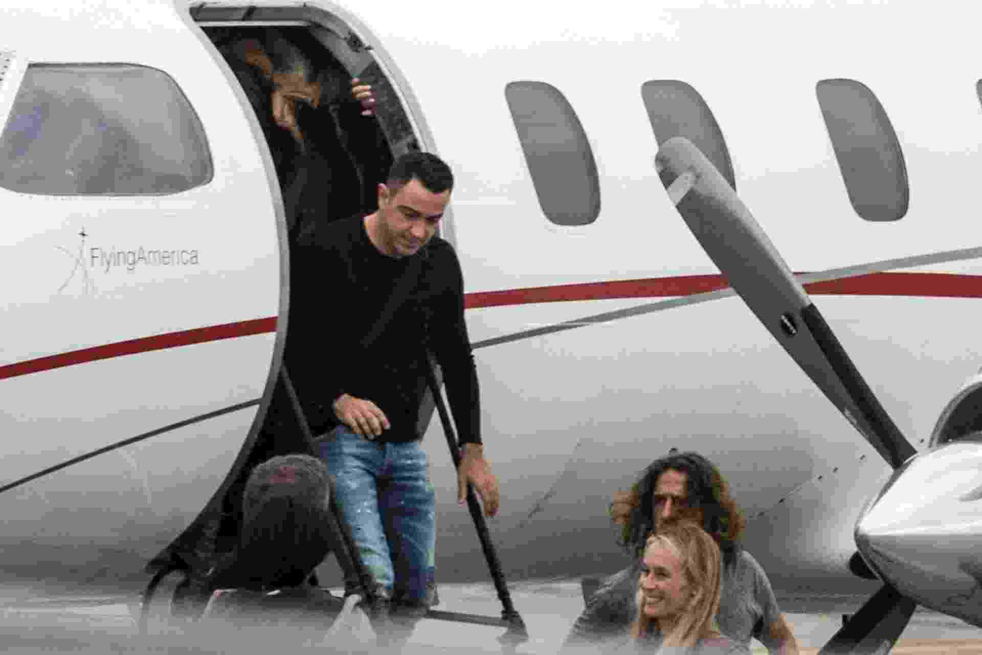 Xavi Hernandez e Carles Puyol desembarcando no aeroporto de Rosário para o casamento de Messi - Marcelo Manera/AFP Photo