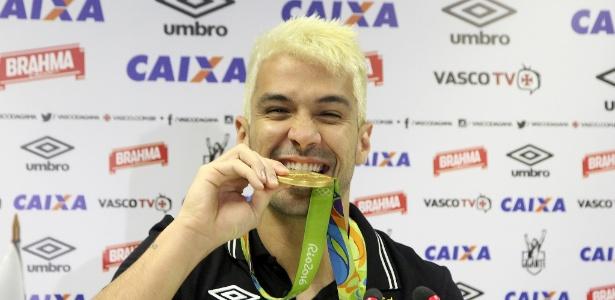 Luan, de cabelo descolorido, morde sua medalha de ouro da Rio 2016