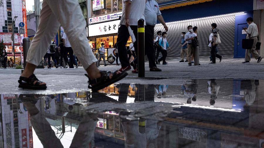 Pessoas andam pela rua em Tóquio durante estado de emergência: taxa de transmissão da covid no Japão supera a do Brasil - YUKI IWAMURA/AFP