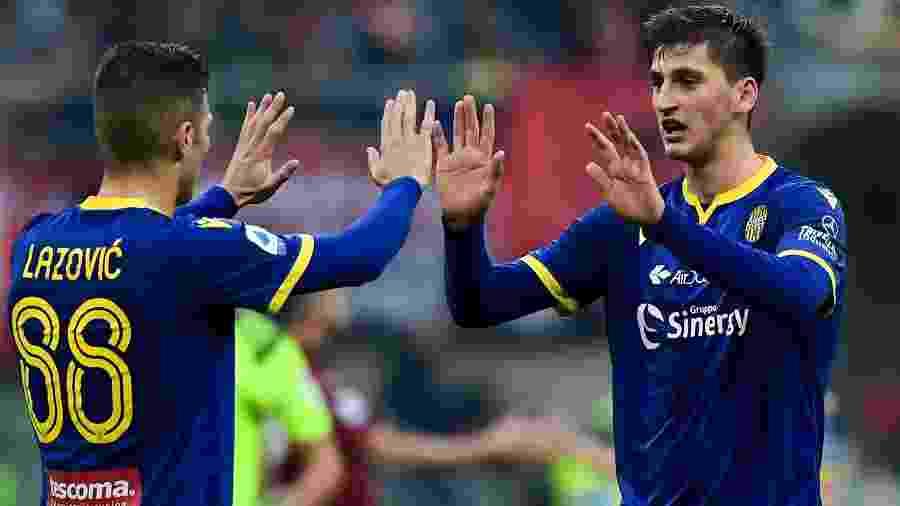 O zagueiro Marash Kumbulla (à direita) cumprimenta o companheiro Darko Lazovic em jogo do Verona contra o Milan, no San Siro - Miguel Medina/AFP