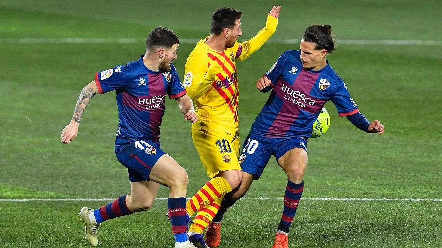 Messi tenta driblar adversários durante vitória do Barcelona sobre o Huesca, pelo Campeonato Espanhol - Pau Barrena/AFP