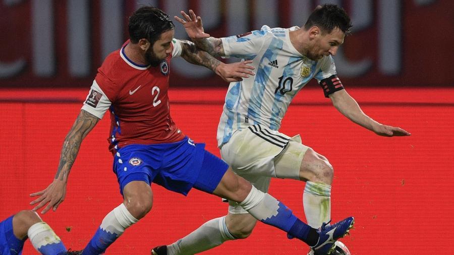 Lionel Messi disputa a bola com Mena durante o jogo entre Argentina e Chile pelas Eliminatórias da Copa  - JUAN MABROMATA/AFP