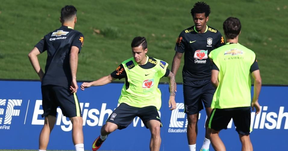 Observado por companheiros, Philippe Coutinho tenta passe em treino da seleção