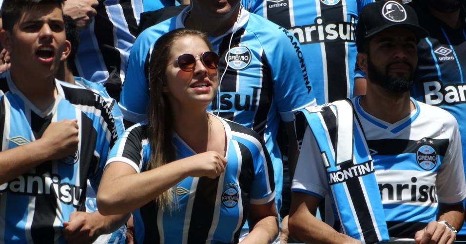 Torcedores do Grêmio cantam enquanto aguardam o time chegar da Argentina