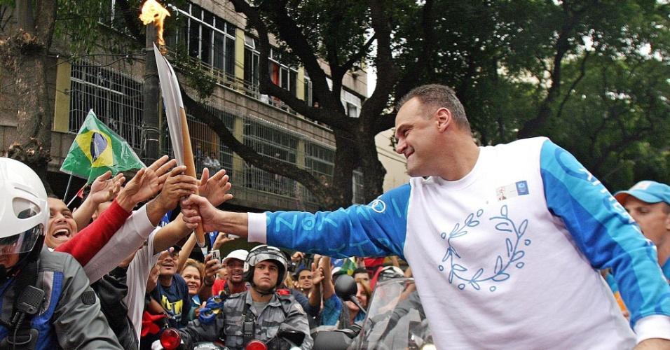 13.jun.2004 - Ex-jogador de basquete Oscar Schmidt participa do revezamento da tocha olímpica dos Jogos de Atenas-2004 no Rio de Janeiro e deixa algumas pessoas tocarem no objeto