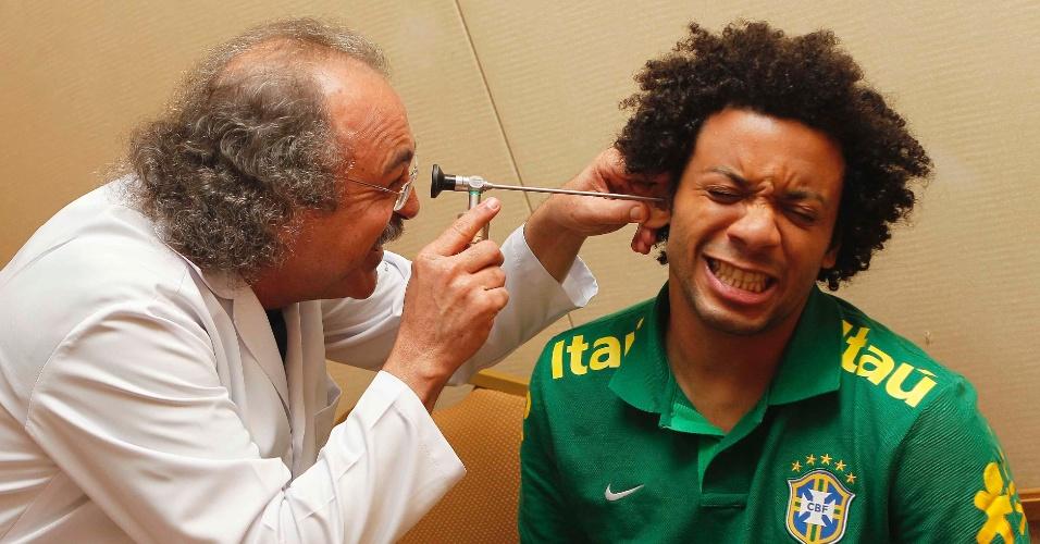 29.mai.2013 - Marcelo brinca e faz cara de dor enquanto é examinado pelo médico da seleção brasileira