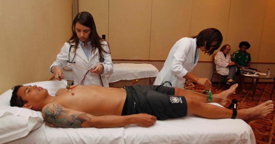 29.mai.2013 - Zagueiro Thiago Silva é examinado por duas médicas da seleção brasileira
