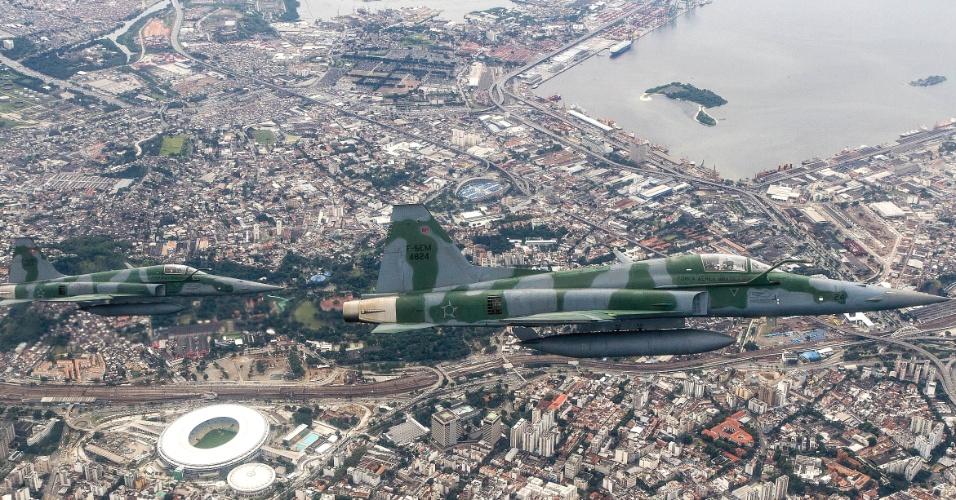 No céu do Rio de Janeiro, dois caças F5M se aproximam de aeronave não identificada para dominar a situação, em exercício da FAB