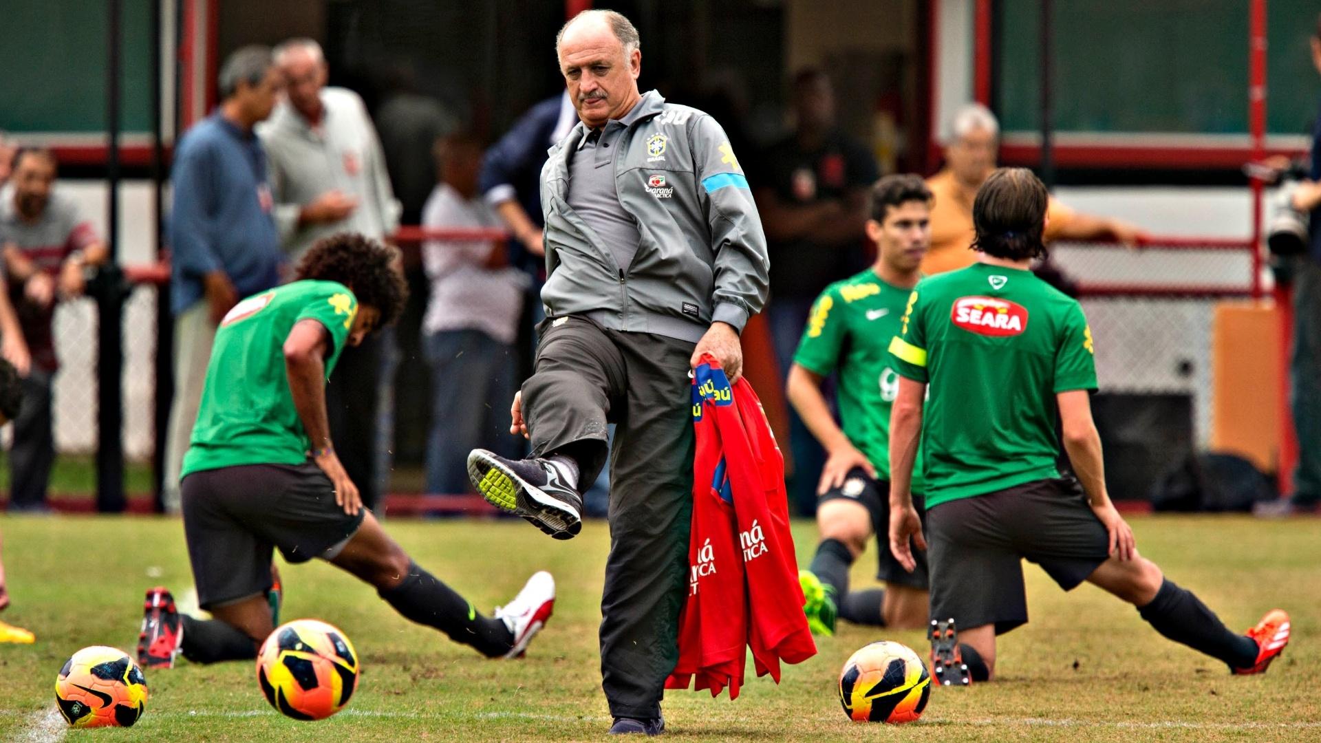 31.maio.2013 - Felipão chuta bolas enquanto jogadores fazem alongamento em treino da seleção nesta sexta-feira