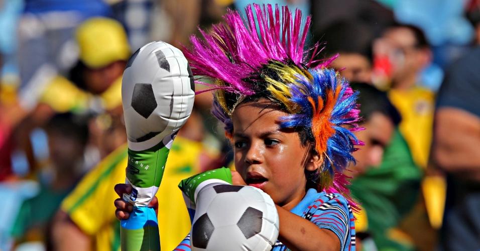 02.jun.2013 - Com peruca colorida, garoto brinca com bastão de plástico antes do amistoso entre Brasil e Inglaterra no Maracanã