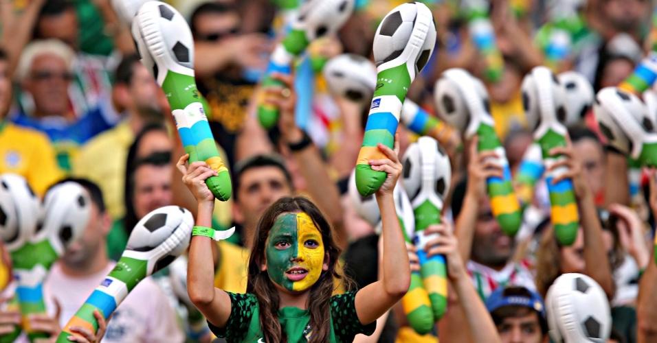 02.jun.2013 - Com rosto pintado de verde e amarelo, jovem torcedora anima arquibancadas do Maracanã