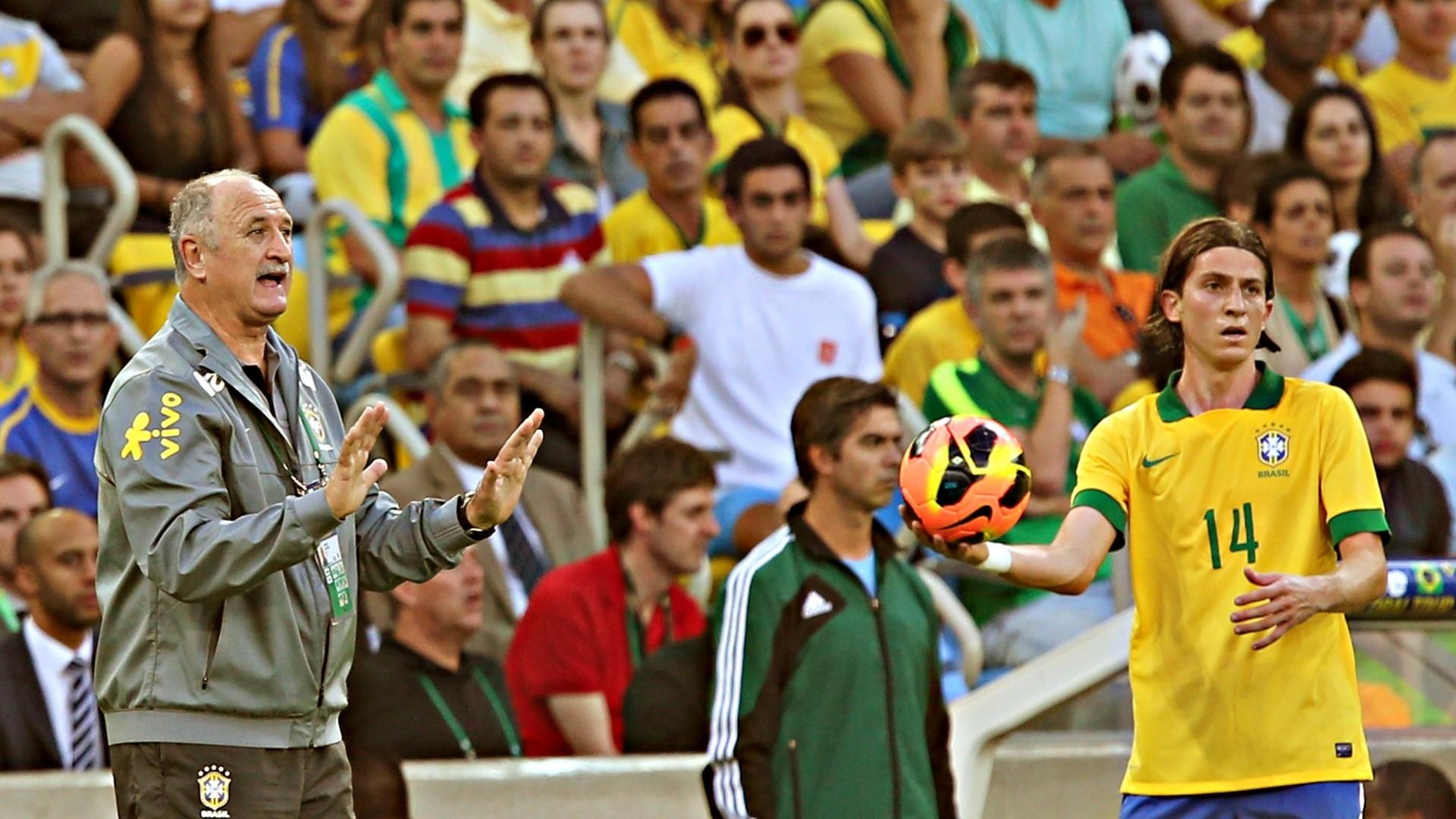 02.jun.2013 - Filipe Luis (e.) obra lateral enquanto Luiz Felipe Scolari orienta os jogadores da seleção contra a Inglaterra