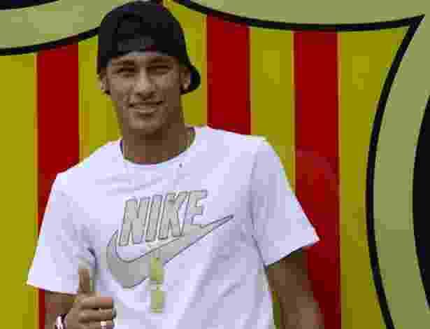 Neymar posa para fotos à frente do escudo do Barcelona - lluis Gene/AFP