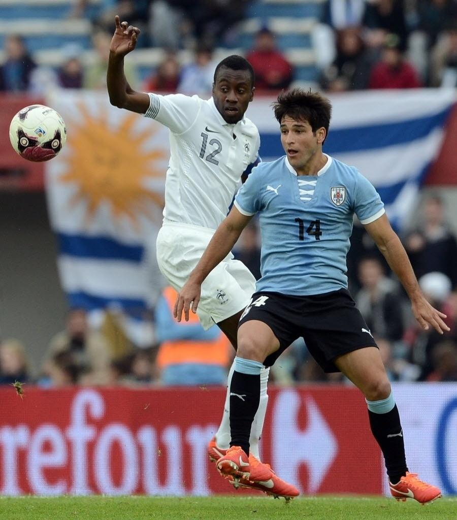 05.jun.2013 - Blaise Matuidi, da França, e Nicolas Lodeiro, do Uruguai, disputam a posse da bola durante amistoso entre as seleções em Montevidéu; uruguaios venceram por 1 a 0