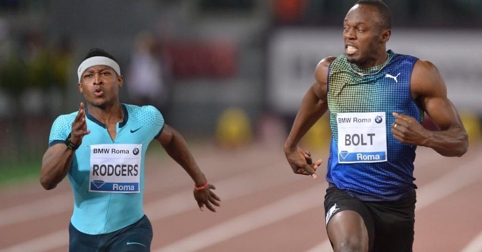 Usain Bolt (dir.) olha para o lado e vê Justin Gatlin (fora da foto) vencendo a prova dos 100 metros rasos da Liga Diamante de Atletismo, em Roma