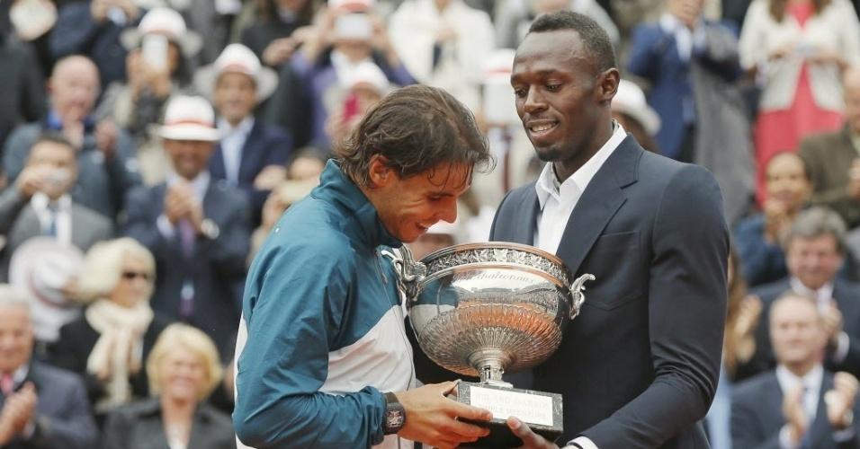 09.jun.2-13 - Usain Bolt entrega o troféu e campeão de Roland Garros 2013 para Rafael Nadal