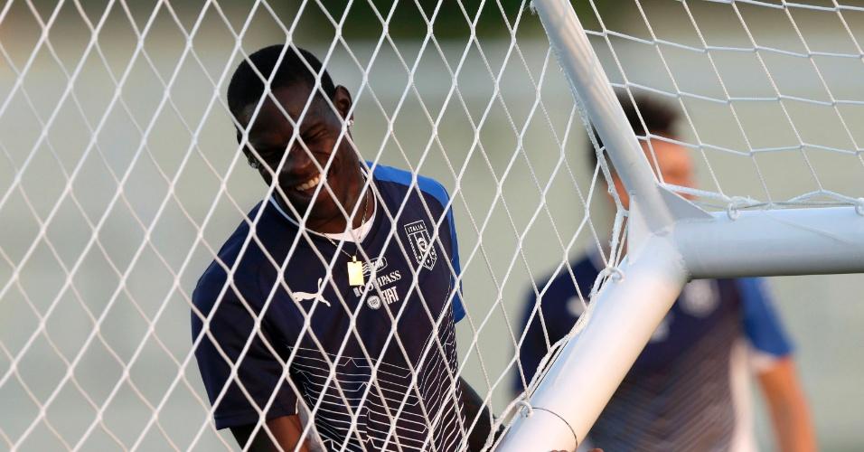 10.jun.2013 - Balotelli ajuda a colocar traves no campo do Engenhão durante treino da Itália
