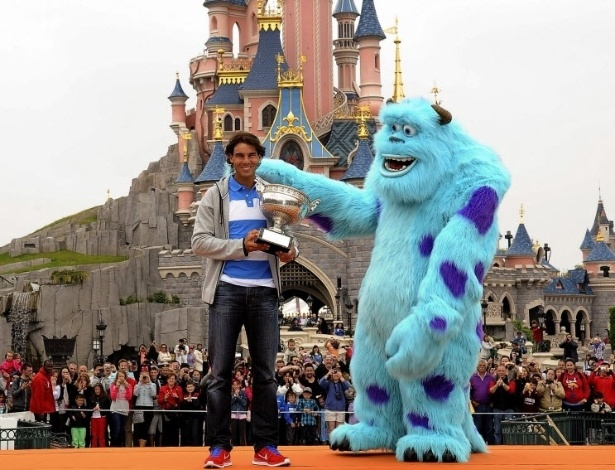 10.jun.2013 - Rafael Nadal visita a Eurodisney, em Paris, e abraça Sulley, personagem do filme Monstros S.A., após ganhar sua oitava taça em Roland Garros