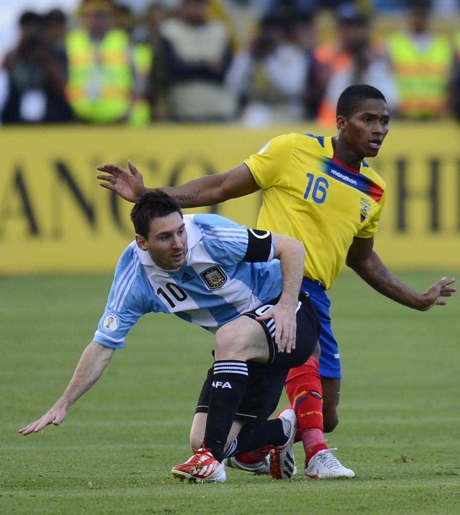 11.jun.2013 - Lionel Messi (e), da Argentina, e Valencia, do Equador, disputam a posse da bola em partida das eliminatórias da Copa-14; jogo terminou 1 a 1