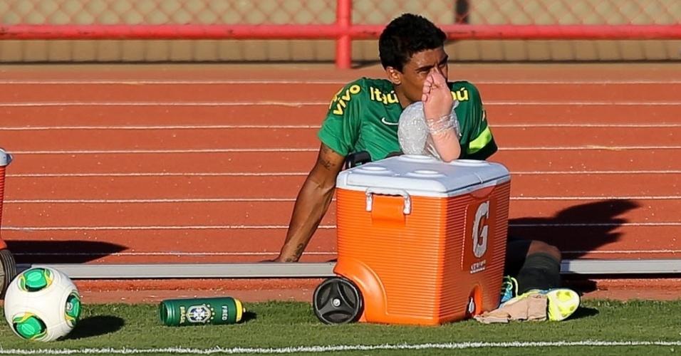 13.jun.2013 - Após torcer o tornozelo, Paulinho fica na beira do campo com gelo na região da lesão