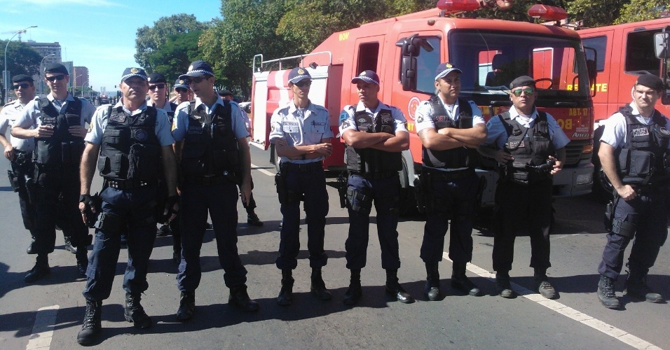 14.jun.2013 - Policiais observam o protesto de manifestantes do Movimento dos Trabalhadores sem teto nos arredores do estádio Mané Garrincha, em Brasília