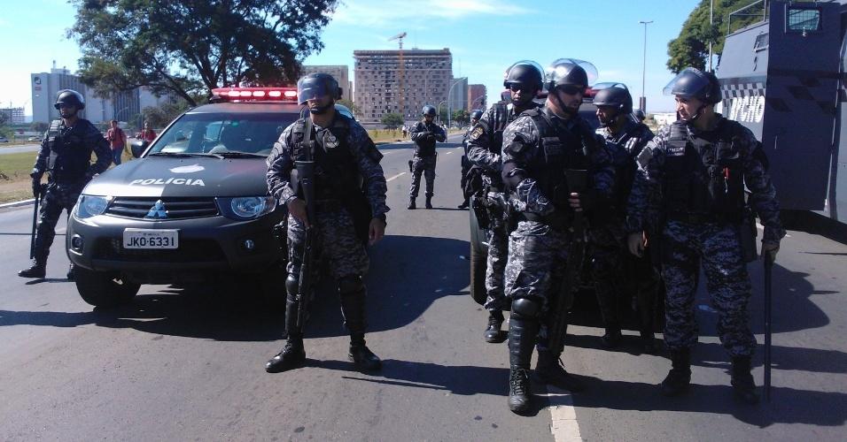 14.jun.2013 - Policiais observam protesto do Movimento dos Trabalhadores Sem Teto na avenida Eixo Monumental, em Brasília, nos arredores do estádio Mané Garrincha