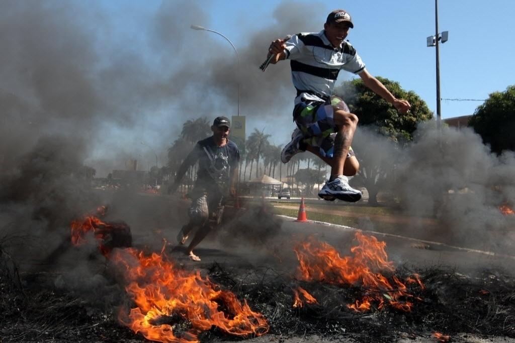 14.jun.2013 - Manifestante pula para passar sobre barricada de pneus nos arredores do estádio Mané Garrincha, em Brasília