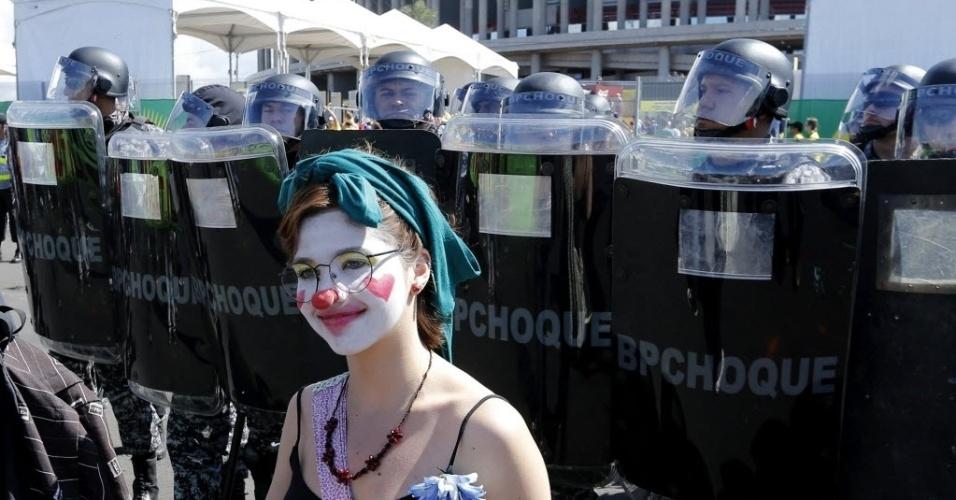 15.jun.2013 - Manifestante pinta o rosto e se fantasia de palhaça para protestar em frente ao estádio Mané Garrincha